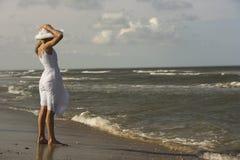 Cappello della holding della ragazza sulla testa alla spiaggia. fotografie stock libere da diritti
