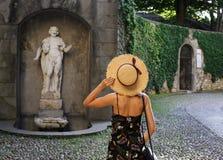 Cappello della tenuta della giovane donna vicino alla statua fotografia stock