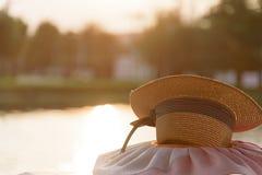 Cappello di Brown al parco ed al fiume del giardino nella sera con il Ti di tramonto Immagine Stock
