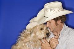 Cappello di cowboy da portare dell'uomo e del cane fotografia stock
