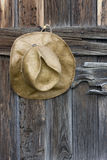 Cappello di cowboy della paglia e legno esposto all'aria Fotografia Stock
