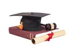 Cappello di graduazione con il martelletto del giudice, del diploma ed il libro Fotografia Stock