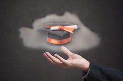 Cappello di graduazione della tenuta della mano su fondo nero Fotografie Stock
