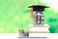 Cappello di graduazione sulla bottiglia di vetro e sui libri sulle sedere verdi naturali fotografia stock libera da diritti