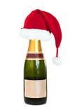 Cappello di Natale su una bottiglia di Champagne con l'etichetta in bianco su bianco Immagini Stock Libere da Diritti