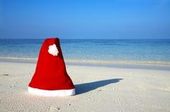 Cappello di natale su una spiaggia Fotografia Stock