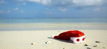 Cappello di natale su una spiaggia Immagini Stock