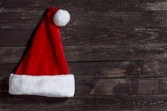 Cappello di Natale sul fondo di legno dello spazio della copia Fotografia Stock