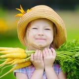 Cappello di paglia d'uso della bambina sveglia che tiene un mazzo di carote organiche fresche Fotografie Stock Libere da Diritti