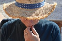 Cappello di paglia d'uso della donna all'aperto, mano sul mento fotografia stock libera da diritti