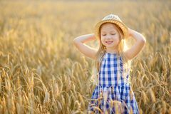 Cappello di paglia d'uso della ragazza adorabile che cammina felicemente nel giacimento di grano sulla sera calda e soleggiata di Fotografia Stock