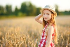 Cappello di paglia d'uso della ragazza adorabile che cammina felicemente nel giacimento di grano sulla sera calda e soleggiata di Immagini Stock