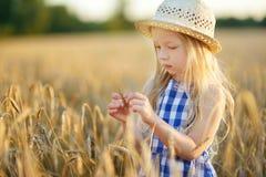 Cappello di paglia d'uso della ragazza adorabile che cammina felicemente nel giacimento di grano sulla sera calda e soleggiata di Fotografia Stock Libera da Diritti