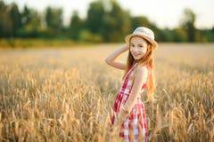 Cappello di paglia d'uso della ragazza adorabile che cammina felicemente nel giacimento di grano sulla sera calda e soleggiata di Immagini Stock Libere da Diritti