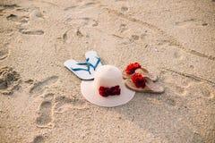 Cappello di paglia della spiaggia una coppia di Flip-flop Oggetti di estate sulla spiaggia sabbiosa immagine stock