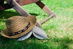 Cappello di paglia e del libro su erba Immagine Stock