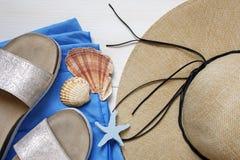 Cappello di paglia, pantofole, asciugamano di spiaggia e conchiglie Fotografia Stock