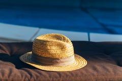Cappello di paglia su sdraio dalla piscina Fotografia Stock