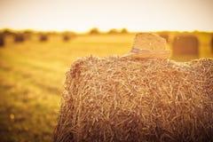 Cappello di paglia su un pacchetto di fieno su un campo nell'ora legale Fotografia Stock