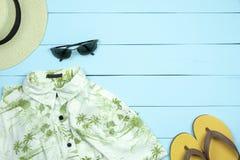 Cappello di paglia, vetri di sole, camicia, Flip-flop su di legno verde chiaro fotografia stock libera da diritti