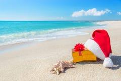 Cappello di Santa Claus e contenitore di regalo di natale sulla spiaggia con il mare Fotografie Stock Libere da Diritti