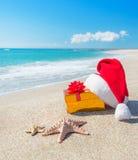 Cappello di Santa Claus e contenitore di regalo di natale sulla spiaggia con il mare Immagini Stock