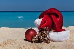 Cappello di Santa Claus e decorazioni di Natale alla spiaggia tropicale, Fotografia Stock Libera da Diritti