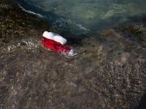Cappello di Santa Claus, nuotante in un'acqua di mare Wi del fondo di Natale Fotografia Stock Libera da Diritti