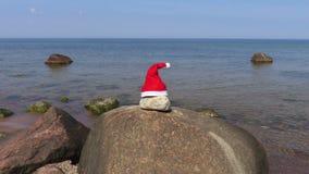 Cappello di Santa Claus sui precedenti del mare di estate video d archivio