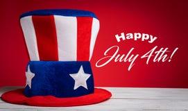 Cappello di zio Sam su fondo rosso con il saluto felice del 4 luglio Fotografia Stock