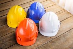 Cappello duro bianco, blu, arancio, giallo della costruzione del casco di sicurezza Fotografia Stock