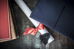 Cappello e diploma di graduazione sulla tavola fotografia stock libera da diritti