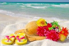 Cappello e fiori sulla spiaggia Fotografie Stock Libere da Diritti