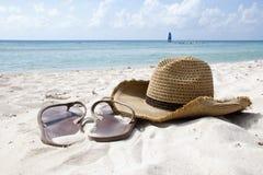 Cappello e Flip Flops della spiaggia sulla riva Fotografie Stock