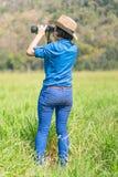 Cappello e tenuta di usura di donna binoculari nel campo di erba Immagine Stock
