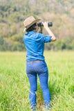 Cappello e tenuta di usura di donna binoculari nel campo di erba Fotografia Stock Libera da Diritti