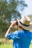 Cappello e tenuta di usura di donna binoculari nel campo di erba Immagini Stock Libere da Diritti