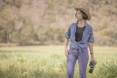 Cappello e tenuta di usura di donna binoculari nel campo di erba Immagini Stock