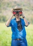 Cappello e tenuta di usura di donna binoculari nel campo di erba Fotografia Stock
