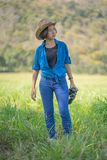Cappello e tenuta di usura di donna binoculari nel campo di erba Fotografie Stock