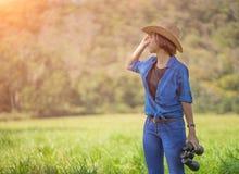 Cappello e tenuta di usura di donna binoculari nel campo di erba Fotografie Stock Libere da Diritti