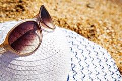 Cappello e vetri bianchi sulla sabbia Fotografie Stock Libere da Diritti