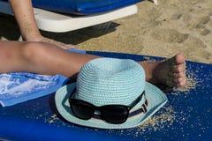 Cappello e vetri sui precedenti della spiaggia Un uomo sta trovandosi su una chaise-lounge del sole fotografia stock