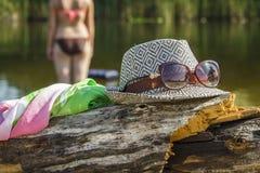 Cappello e vetri sulla banca sabbiosa del fiume Fotografia Stock Libera da Diritti