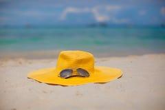 Cappello ed occhiali da sole del primo piano sulla spiaggia dentro Immagine Stock