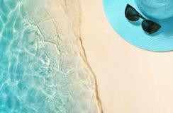 Cappello ed occhiali da sole sulla spiaggia sabbiosa Fondo di estate immagine stock libera da diritti