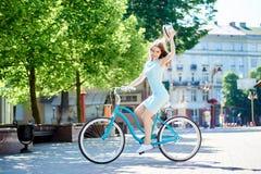 Cappello femminile attraente sorridente della tenuta mentre guidando bici blu nel centro urbano pavimentato fotografia stock libera da diritti