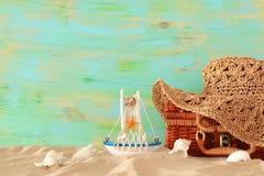 Cappello femminile di modo della spiaggia sopra la valigia della paglia nella sabbia Concetto tropicale di vacanze estive fotografia stock libera da diritti