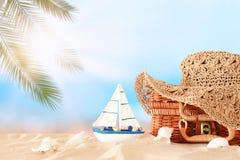 Cappello femminile di modo della spiaggia sopra la valigia della paglia nella sabbia Concetto tropicale di vacanze estive fotografie stock