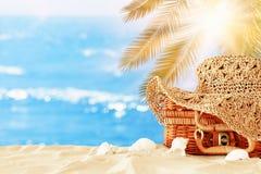 Cappello femminile di modo della spiaggia sopra la valigia della paglia nella sabbia Concetto tropicale di vacanze estive immagine stock libera da diritti